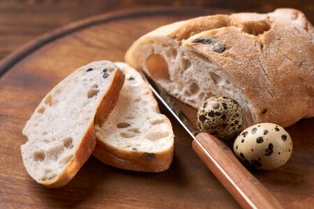 Ciabatta with olives. Fresh diet homemade bread baked according to a traditional Italian recipe, quail eggs. Healthy eating, organic farm food. Rustic table, wooden cutting board. Knife for bread.