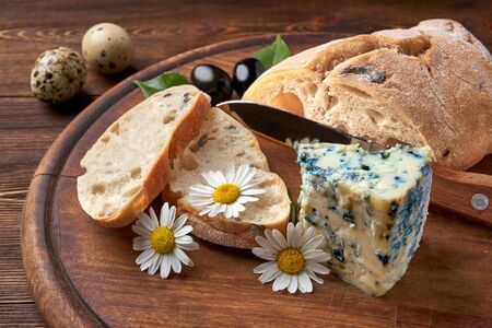 Sliced homemade ciabatta, blue gorgonzola cheese, olive branch and quail eggs. Chamomile flowers and a bread knife. Fresh diet healthy food in Italian tradition. Farm food. Wooden Foto de archivo