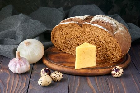 Pumpernickel - bread made with a combination of rye flour and whole rye grains. Quail eggs, cheese, white onion and garlic. Rustic style, wooden cutting board, linen, pine table. Fresh healthy farm food. Zdjęcie Seryjne