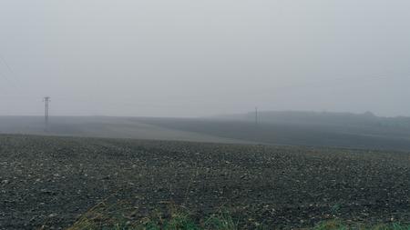 torres de alta tension: empty black soil field with pylons in heavy fog