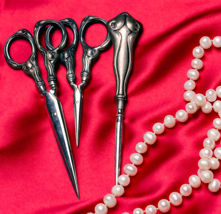 Antique sewing tools and a pearl necklace on a red silk