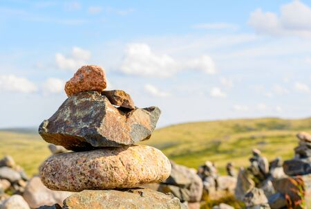 Pyramid of stones in the Murmansk region, near Teriberka. In the background, blue sky and green meadows-moss and lichen, small plants of Northern latitudes Zdjęcie Seryjne