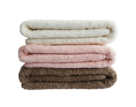 Bath towels in stack. White, pink, brown.