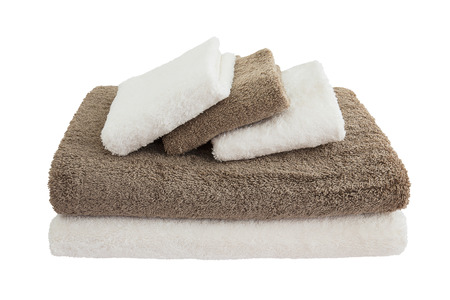 absorb: white and brown bath towels in stack isolated over white Stock Photo