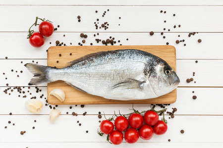 sparus: Fresh dorado fish on wooden cutting board with tomatoes