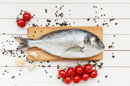 peces: Pescados frescos del dorado sobre tabla de cortar de madera con tomates Foto de archivo