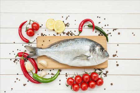 Fresh dorado fish with lemon on wooden cutting board photo