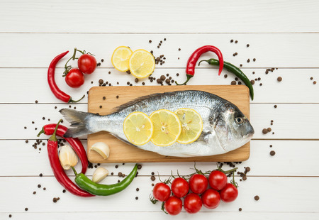 Dorado fish on wooden cutting board with cherry tomatoes photo