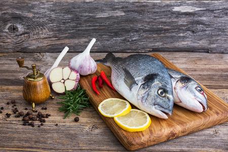dorado fish: Fresh dorado fish on wooden cutting board with lemon and garlic