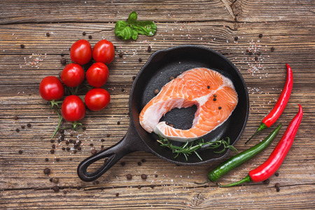 salmon steak: Salmon steak in pan on old wooden background. Top view. Toned Stock Photo