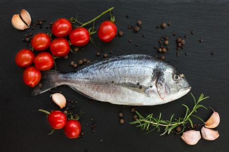 gilthead bream: Fresh dorado fish on slate cutting board with cherry tomatoes, rosemary and garlic Stock Photo