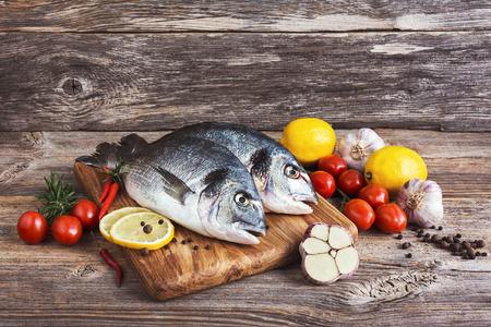 dorada: Fresh dorada fish on wooden cutting board with vegetables Stock Photo