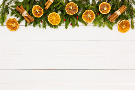 christmas symbol: Christmas background. Christmas fir tree, dried oranges on white wooden background with copy space. Stock Photo