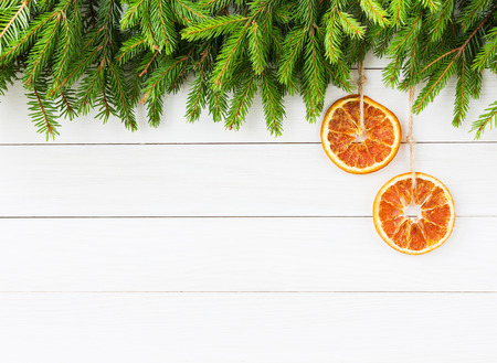orange color: Christmas background. Christmas fir tree with orange decoration on white wooden board background with copy space