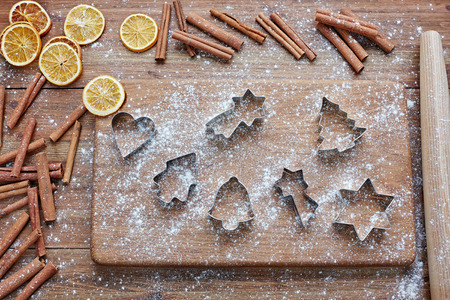 pastry cutters: Pastry cutters on wooden cutting board, cinnamon sticks