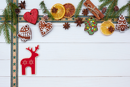 Christmas background. Christmas white wooden background with Christmas cookies, cinnamon and deer
