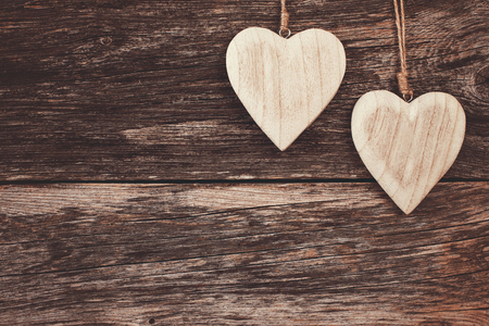 Twee houten harten op houten achtergrond. Kopieer ruimte, soft focus, getinte, vintage stijl