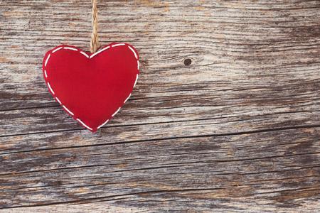 Corazón rojo sobre fondo de madera. Entonado, estilo vintage, espacio de copia Foto de archivo