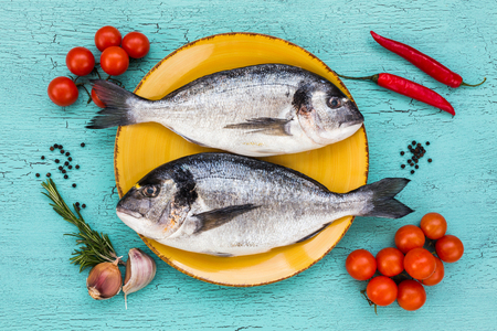sparus: Two fresh dorado fish on yellow plate and vegetables on blue table. Top view. Stock Photo