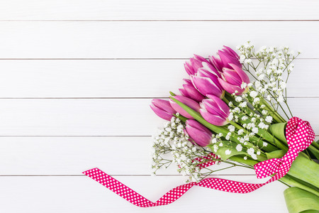 Bouquet of bright pink tulips and gipsophila decorated with ribbon on white wooden background. Top view, copy space Stock Photo