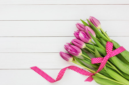 pink tulips: Bouquet of bright pink tulips on white wooden background. Top view, copy space