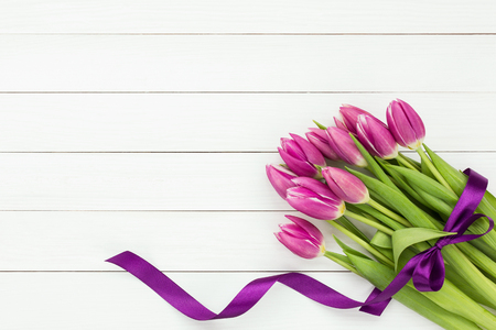 pink tulips: Bouquet of pink tulips decorated with purple ribbon on white wooden background. Top view, copy space