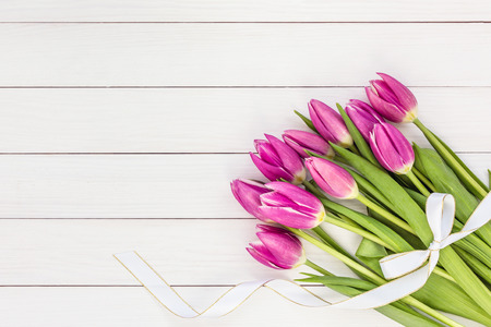 pink tulips: Bouquet of bright pink tulips with white ribbon on white wooden background. Top view, copy space