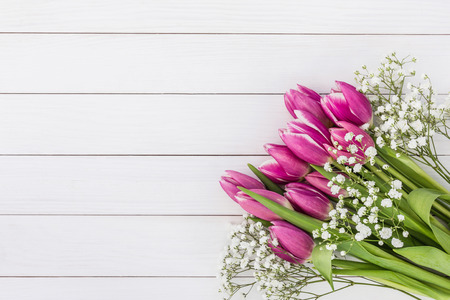 pink tulips: Bouquet of pink tulips and gipsophila flowers on white wooden background. Top view, copy space