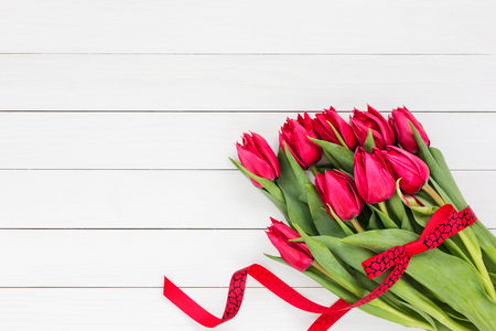 Bouquet of red tulips with red ribbon on white wooden background. Top view, copy space