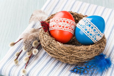 Colorful Easter eggs decorated with lace in small nest, willow branch