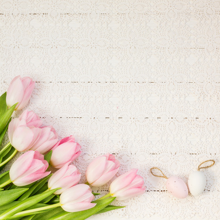 Pink tulips and decorative Easter eggs on white tablecloth. Top view, copy space Фото со стока