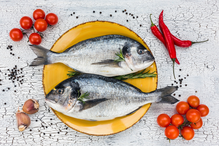 sparus: Raw fresh dorado fish on yellow plate and vegetables on white table. Top view. Stock Photo
