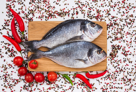 Raw dorado fish on wooden cutting board with vegetables. Top view, copy space Stock Photo