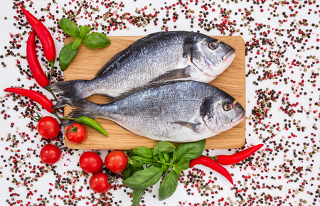 Raw dorado fish on wooden cutting board with peppercorns on white table. Top view, copy space Stock Photo