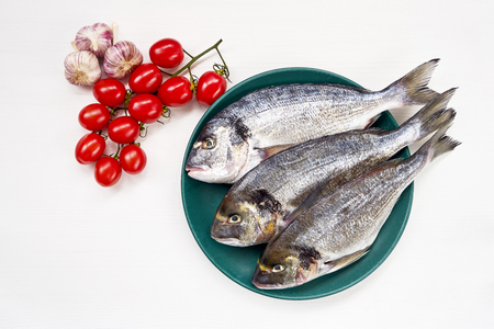 Raw dorado fish on green plate on white table. Top view, copy space Stock Photo