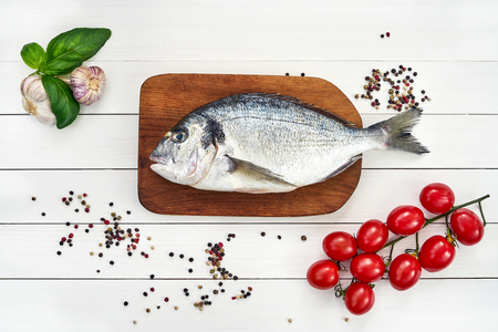 Fresh dorado fish on wooden cutting board with garlic, tomatoes and peppercorns. Top view, copy space Stock Photo