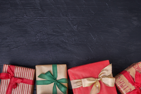 Wrapped gifts boxes decorated with ribbon on black  wooden background. Copy space, top view Stock Photo