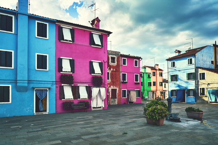 Burano, Venice. Old colorful houses architecture at the square with fountain. Summer 2017, Italy. Cloudy weather, toned