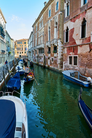 Traditional narrow canal with gondolas and boats in Venice, Italy