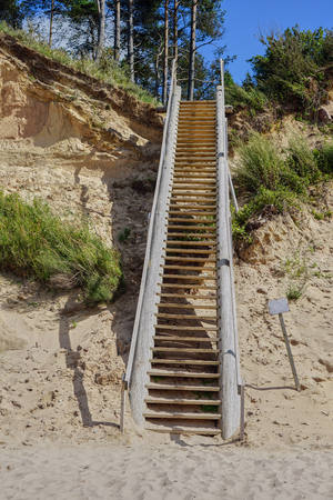Latvia. Baltic sea. Jurkalne. Wooden stairway to steep dune shore. Sand dunes with pine trees. Stock Photo