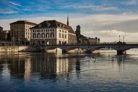 View of historic city of Zurich. Munsterbucke bridge crossing river Limmat, Canton of Zurich, Switzerland. Cloudy day