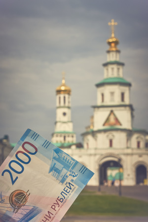 Russian money 2000 thousand rubles on the background of the Orthodox Church. Toned image, copy space. Blurred, soft focus