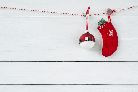 Red Christmas ornaments on white wooden background. Red Christmas sock with decoration. Copy space