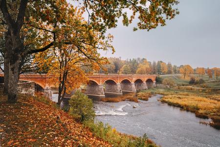 Autumn landscape. The Old Brick Bridge across the Venta river in Kuldiga, Latvia. Overcast weather