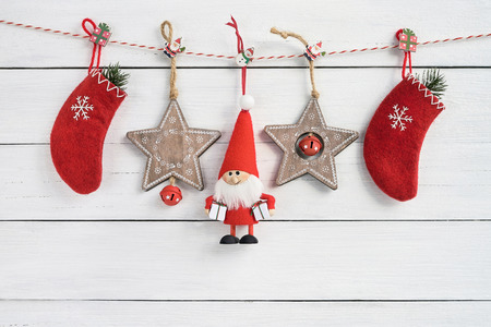 Christmas decoration on white wooden background. Copy space. Santa Claus, Christmas socks and wooden stars on white background.