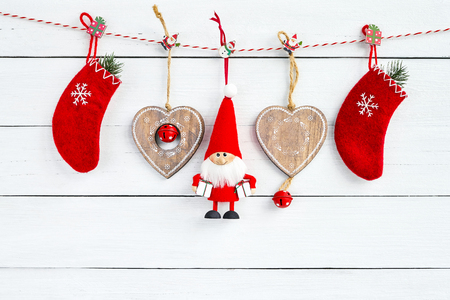 Christmas decoration with Santa on white wooden background. Red Christmas socks, Santa Claus and Christmas hearts. Copy space Фото со стока