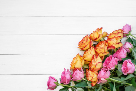 Pink and yellow roses on white wooden background. Bouquet of colorful roses. Copy space, top view. Greeting card.