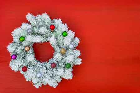 Red Christmas background. White Christmas wreath with Christmas ornaments on red background. Top view, copy space