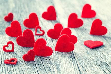 Valentines Day background. Red hearts on wooden background. Selective focus, toned image. Greeting card