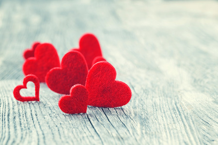 Valentines Day background. Red hearts on wooden background. Selective focus, toned image. Фото со стока
